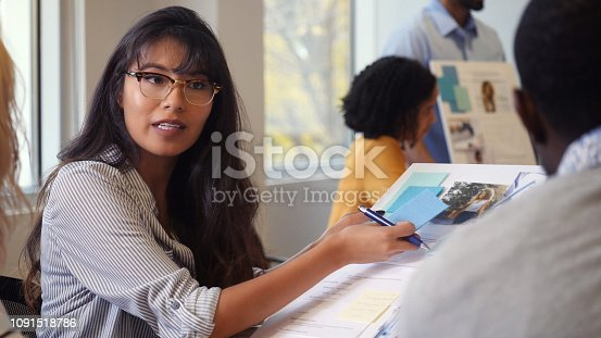 Young Hispanic female creative professional discusses current project with male colleague.