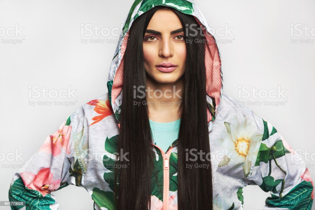 Serious determined young woman with hands on hips stock photo