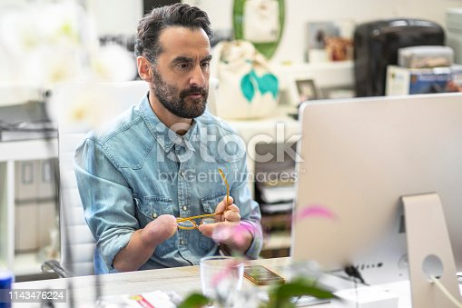 Serious mature businessman looking at computer. Disabled design professional sitting at desk. He is in creative office.