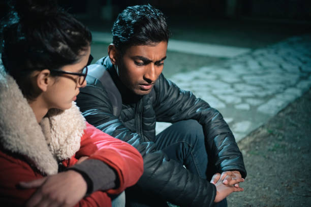 Serious discusses between young woman and man. Asian, Indian unhappy young man and woman discusses something serious together and they sit in park at night. between stock pictures, royalty-free photos & images
