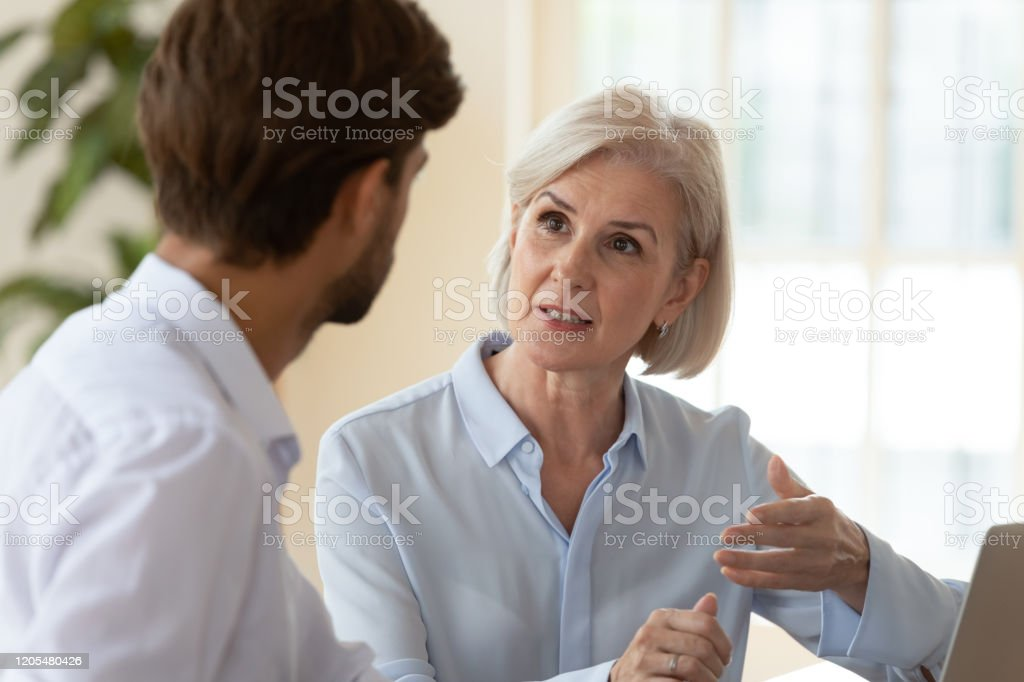 Seriöse, vielfältige Geschäftsleute diskutieren Ideen bei Meetings - Lizenzfrei Alter Erwachsener Stock-Foto