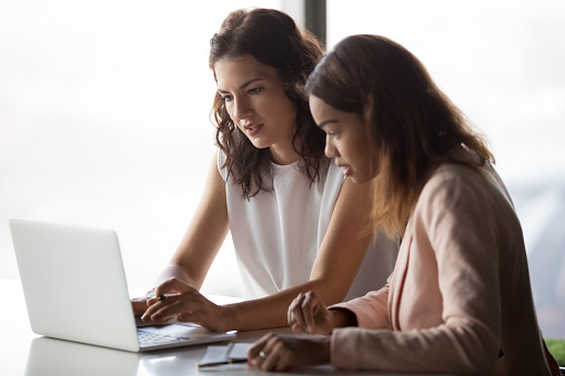 istock Serious diverse businesswomen discussing online project together looking at laptop 1128967589