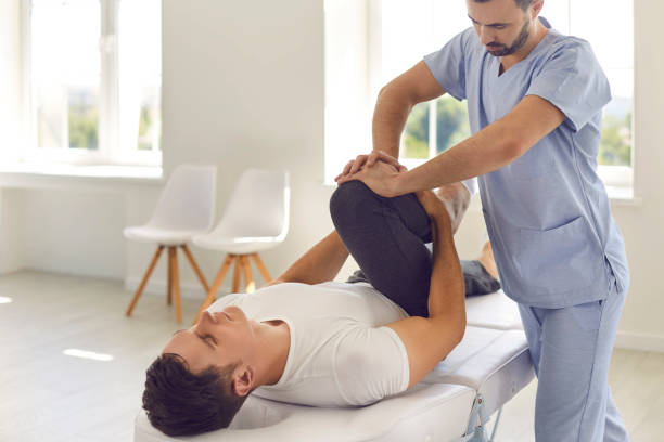 Serious doctor helping male athlete do physical exercise during rehabilitation after leg injury stock photo