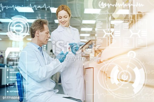 istock Serious doctor holding a test tube while his colleague looking at it 917715318