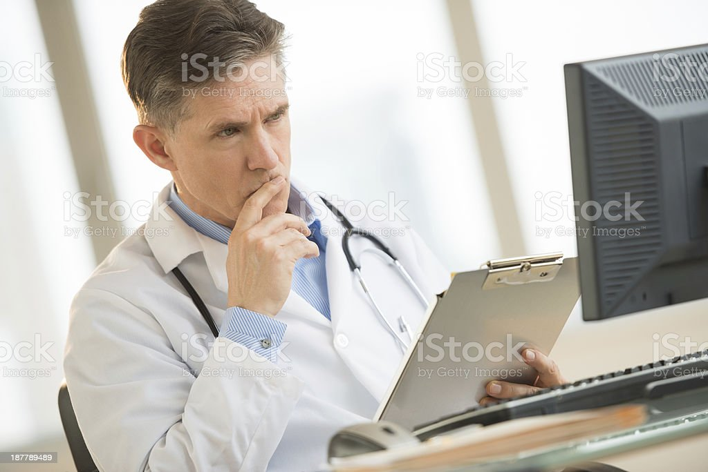 Serious Doctor Looking At Computer While Holding Clipboard In clinic stock photo