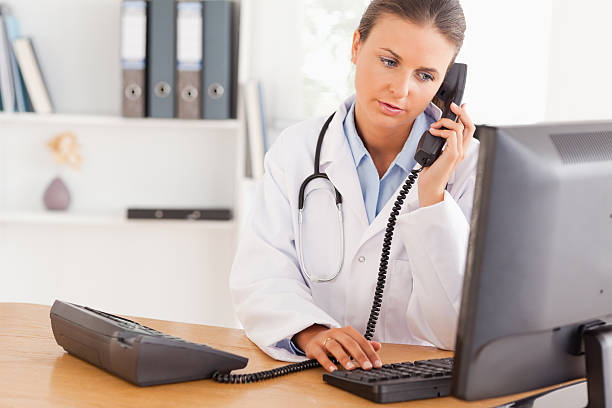 serious doctor on the phone - nurse on phone stock photos and pictures