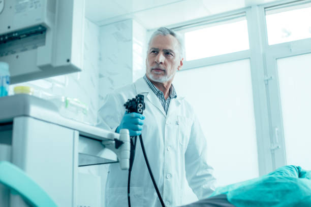Serious doctor performing endoscopy in his clinic stock photo