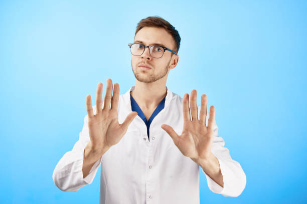 Serious doctor shows a gesture with his hands to the camera, stop panic, keep calm concept isolated on blue background