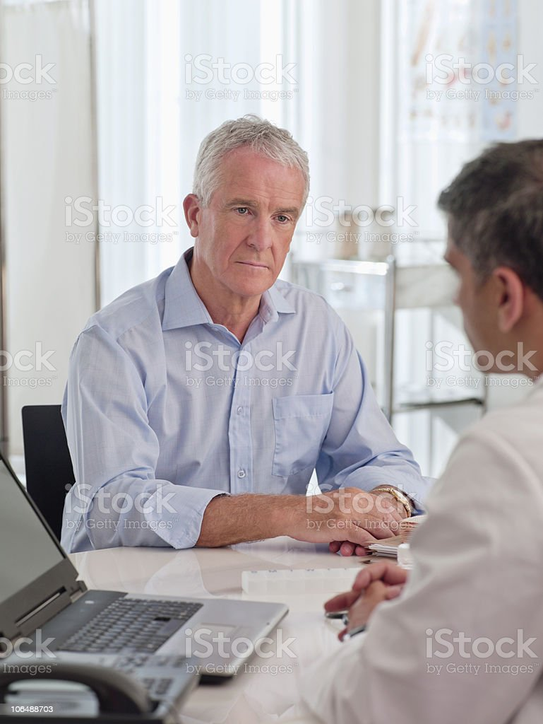 Serious doctor with his patient sitting in hospital royalty-free stock photo