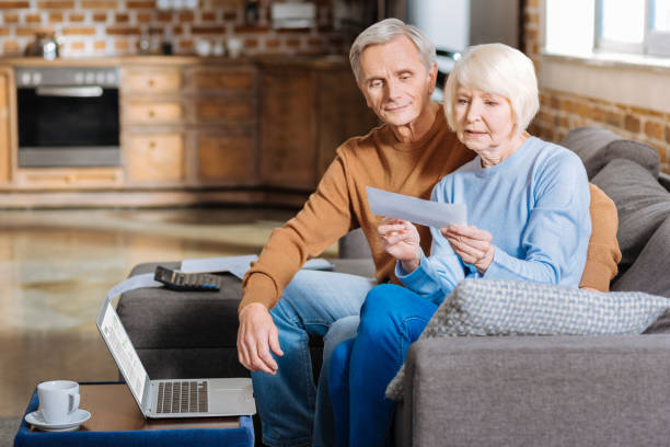 Serious elderly woman checking financial documents Payment notification. Serious unhappy elderly woman sitting together with her husband and looking at the document while holding it social security stock pictures, royalty-free photos & images