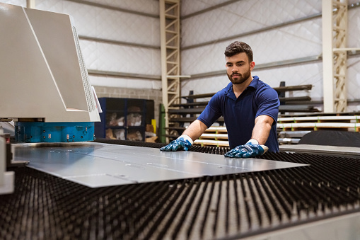 Serious Engineer Adjusting Metal On Puller Machine Stock Photo - Download Image Now