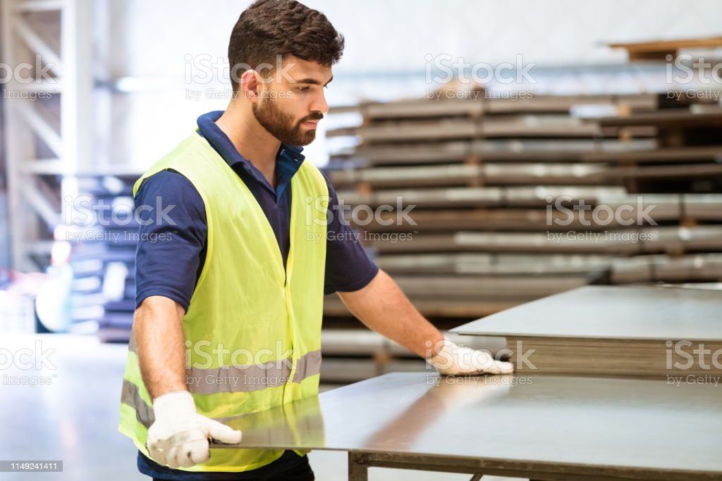 Serious engineer adjusting metal sheet in industry Serious young engineer adjusting metal sheet on machinery. Male apprentice is in protective workwear. He is working in manufacturing industry. 20-24 Years Stock Photo