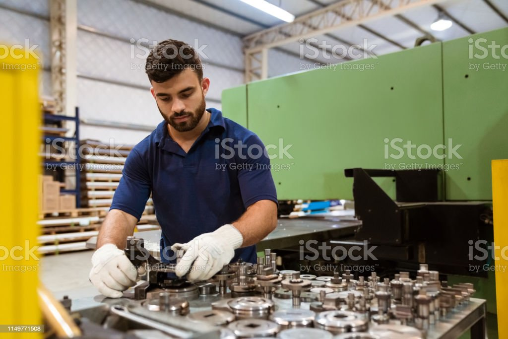 Serious engineer using manufacturing machinery Serious male engineer using manufacturing machinery. Young apprentice is wearing uniform. He is working in metal industry. 20-24 Years Stock Photo