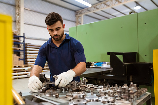 Serious Engineer Using Manufacturing Machinery Stock Photo - Download Image Now