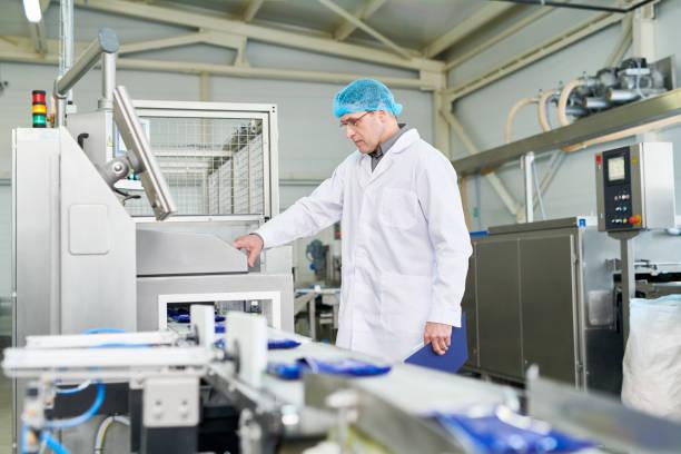 Technologue alimentaire mâles expérimentés sérieux dans les vêtements stériles modifier le programme de ligne de production tout en travaillant dans la boutique de l'emballage - Photo