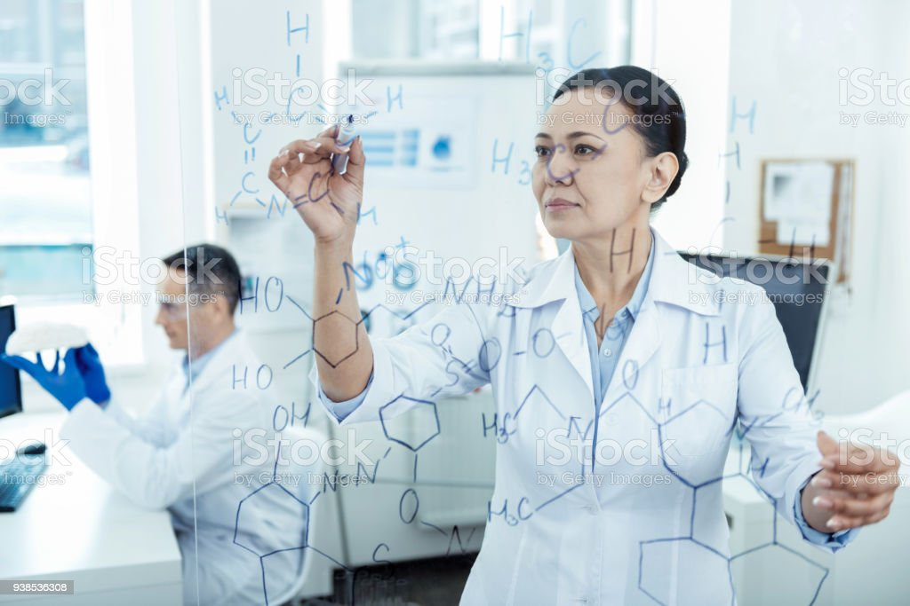 Serious experienced researcher writing a formula stock photo