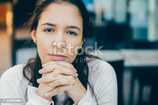 Serious face of young Latin American woman sitting at cafe. Close-up of businesswoman or female student with clasped hands looking at camera. Young woman concept