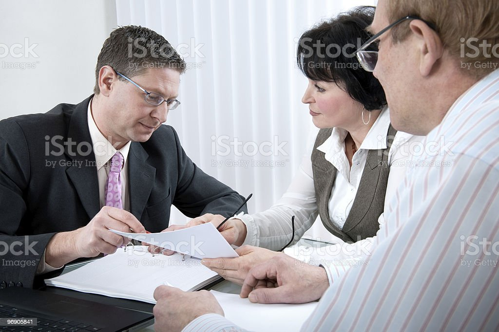 Serious faced business people looking at paper in a meeting royalty-free stock photo