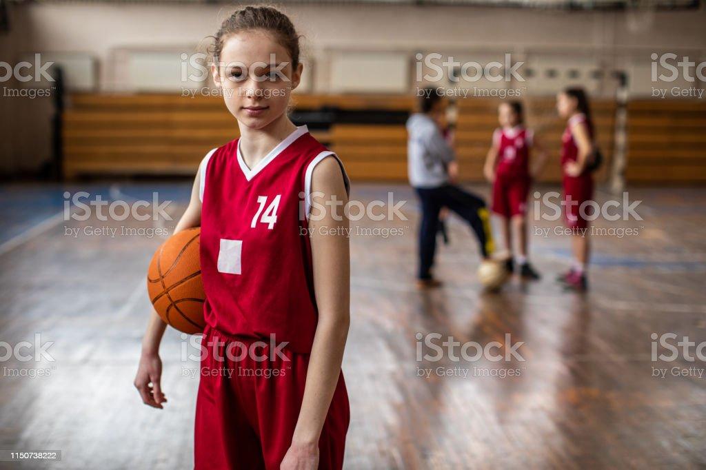 Serious female basketball player in sport uniform holding sport ball...