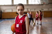 Serious  female basketball player  in sport uniform holding sport ball and looking at camera