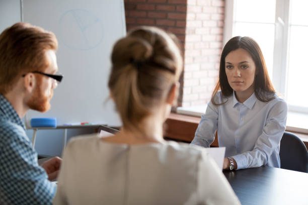 serious female boss listening to employees reporting about work results - assertiveness stock pictures, royalty-free photos & images