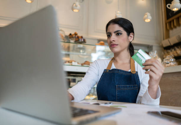 serious female business owner of a bakery shopping online with her credit card - business credit card stock photos and pictures