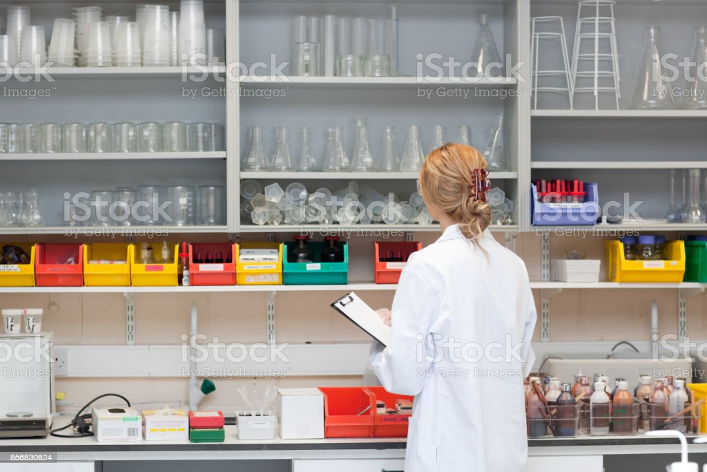 Serious female scientist writing on her clipboard stock photo