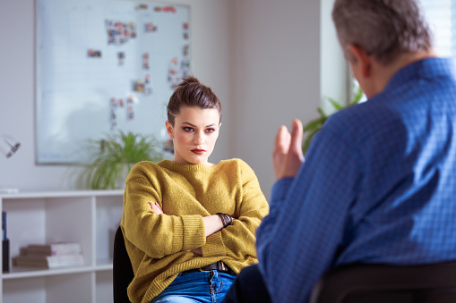 Serious Female Student Listening To Therapist Stock Photo - Download Image Now
