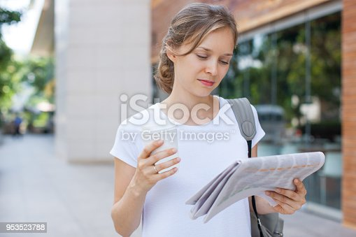 istock Serious female student walking with coffee and reading newspaper 953523788