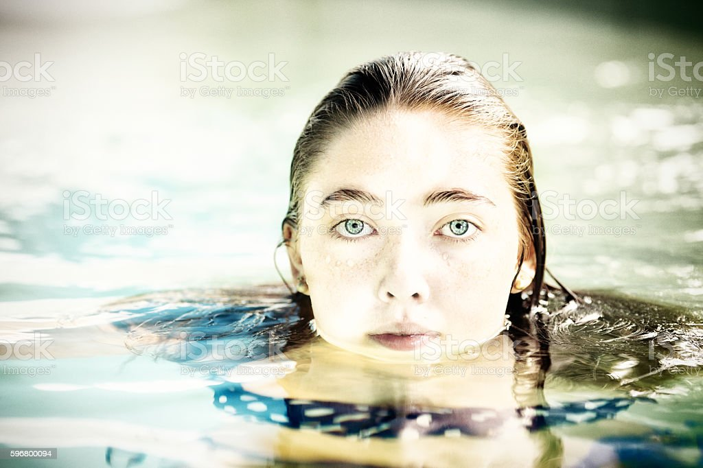 Serious female teenager portrait emerging from water.