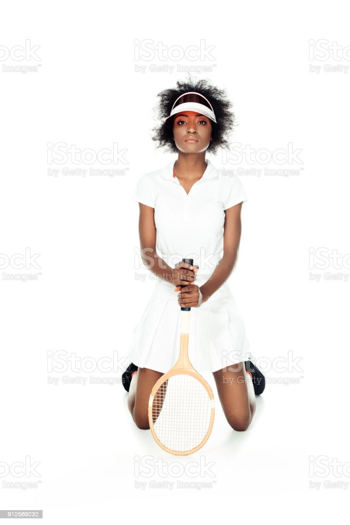serious female tennis player with racket standing on knees isolated on white stock photo