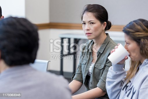 istock Serious female veteran during support group meeting 1173363345