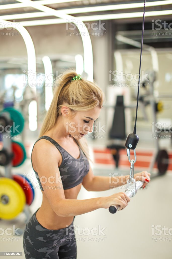 serious fit woman doing exercises on the lat row in the sport center....