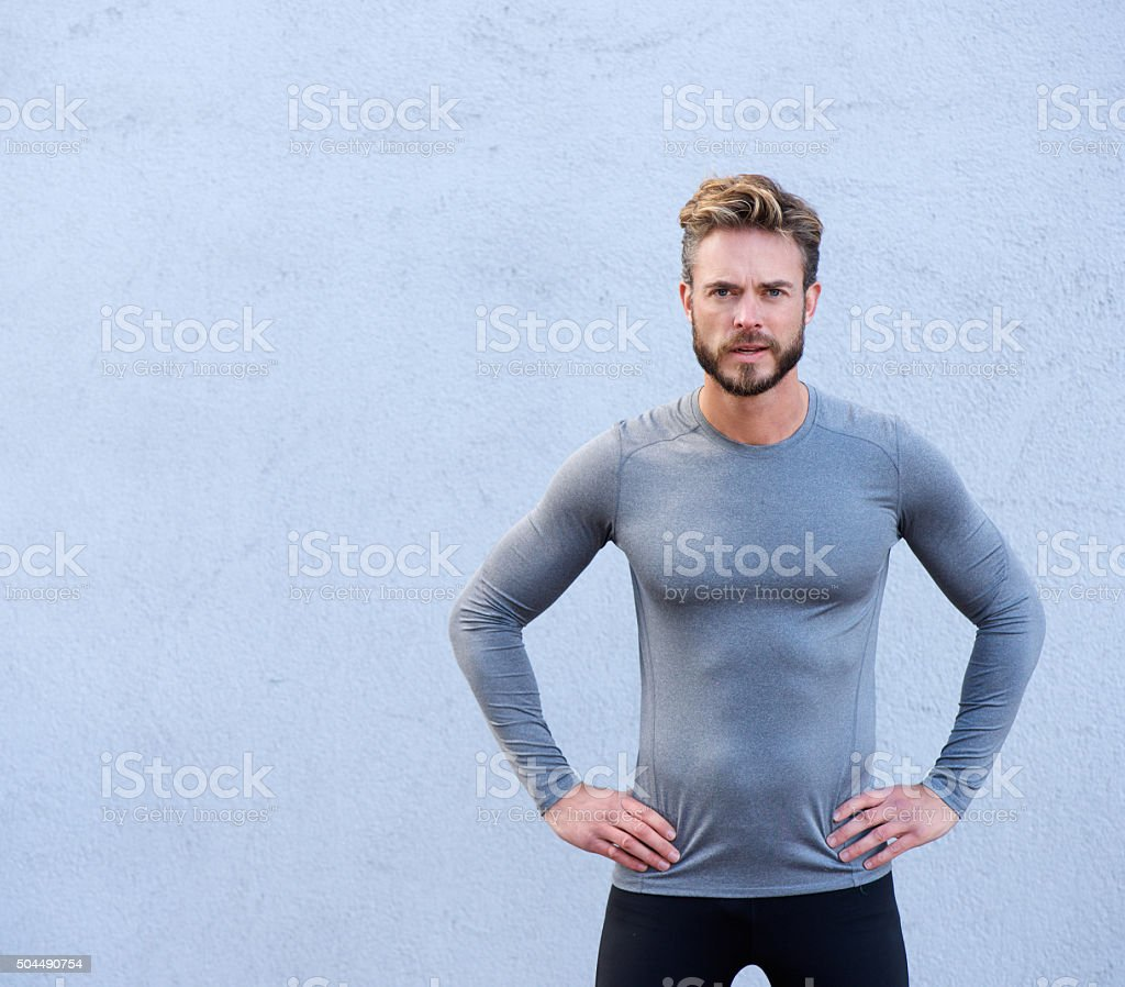 Serious fitness trainer standing against gray background stock photo