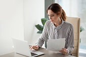 istock Serious focused businesswoman typing on laptop holding papers preparing report 1129638600