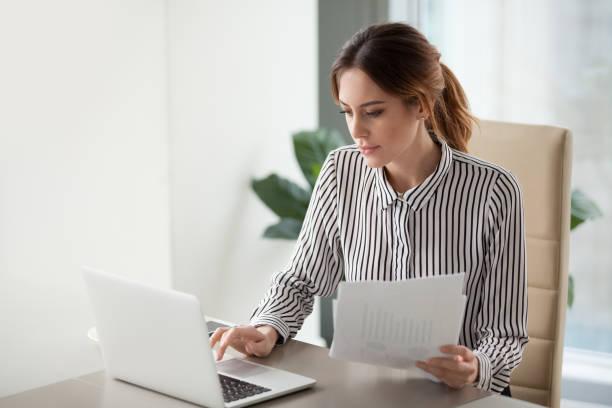 ernsthafte fokussierte geschäftsfrau auf laptop halten papiere bericht schreiben - leitende position stock-fotos und bilder