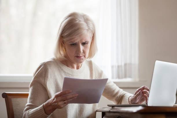 sérieuse frustrée moyenne femme âgée troublée avec des factures domestiques - facture photos et images de collection