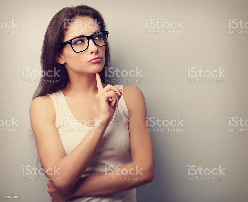 Serious fun thinking young woman looking up stock photo