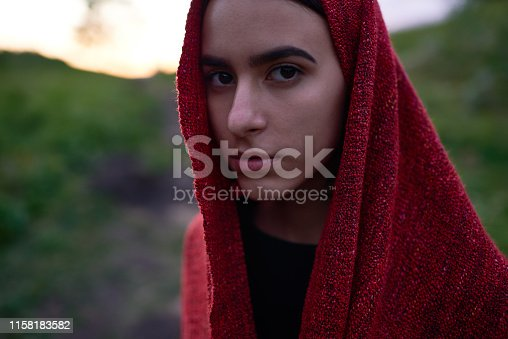 Portrait of young serious brunette in red covering looking at camera on blurred nature background