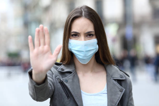 Serious girl doing stop sign with mask on street stock photo