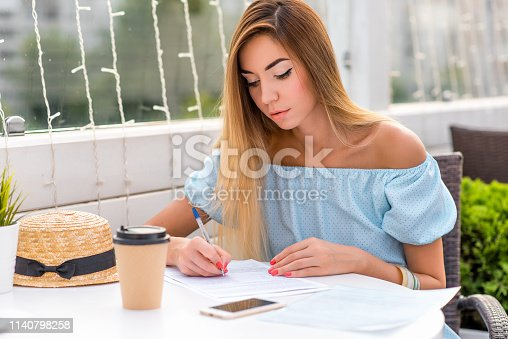 istock Serious girl fills paper contract. Blue dress hair business lady. Summer restaurant woman writes signature important contract. Concept transaction, notary certification agreement meeting diplomacy. 1140798258
