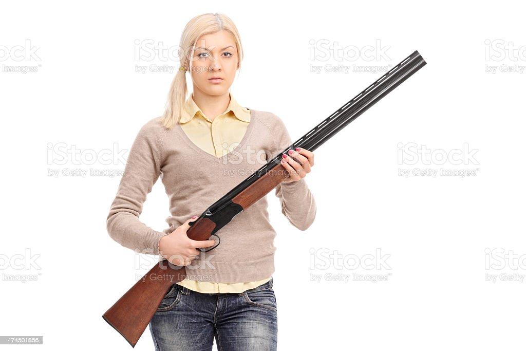 Serious girl holding a shotgun stock photo