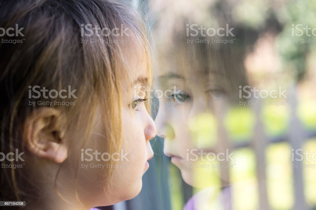 Serious girl looking through a window stock photo