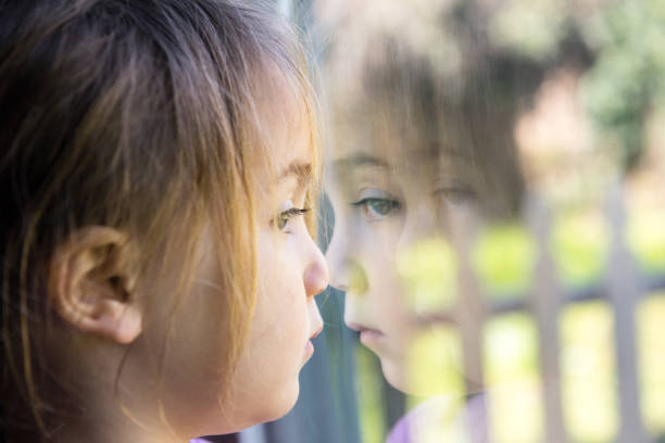 serious girl looking through a window - autism stock photos and pictures