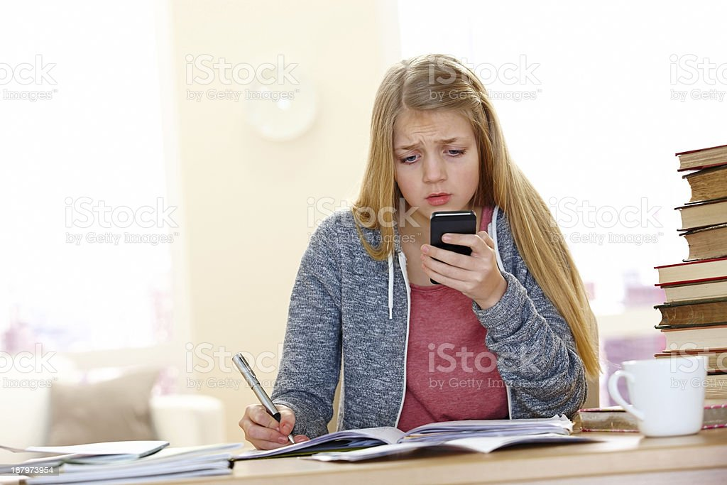 Serious girl reading text message while doing homework royalty-free stock photo
