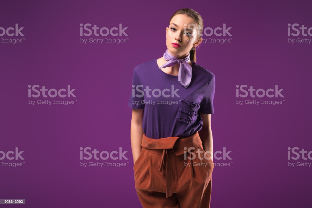 serious girl with hands in pockets looking at camera isolated on purple stock photo