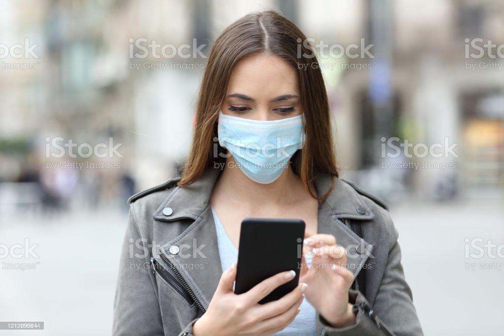 Ernsthafte Mädchen mit Maske überprüfen ihr Handy auf der Straße - Lizenzfrei Am Telefon Stock-Foto