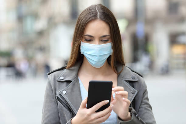 Serious girl with mask checking her phone on street stock photo