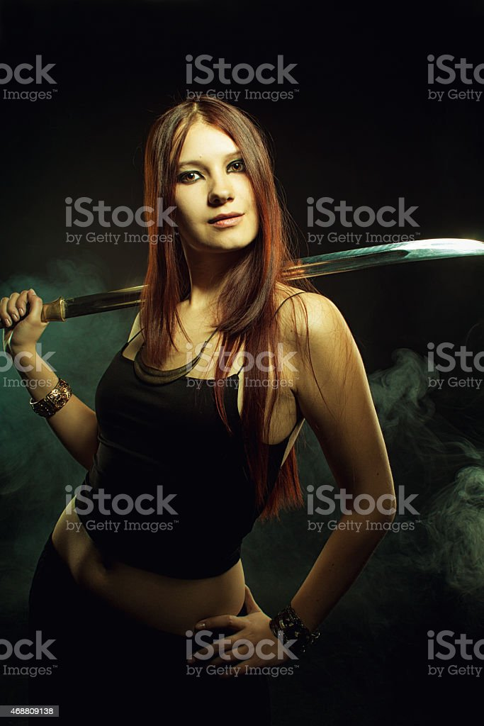 Serious girl with sword stock photo
