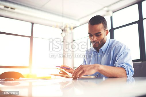 istock Serious good looking creative journalist thinking about new article for publication sitting in coworking space,talented concentrated architect planning work for project and writing ideas in notepad 903783632